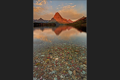 Sinopah Mountain spiegelt sich bei Sonnenaufgang im Two Medicine Lake in Waterton Glacier, Wyoming
