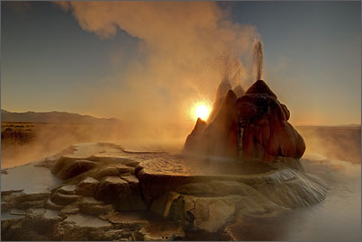 Fly Geyser is spouting boiling water fountains into the back light of the morning sun in the Black Rock Desert of Nevada.