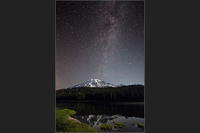 Nighttime Mount Rainier volcano mirrors with the stars of the Milky Way in the Reflection Lakes