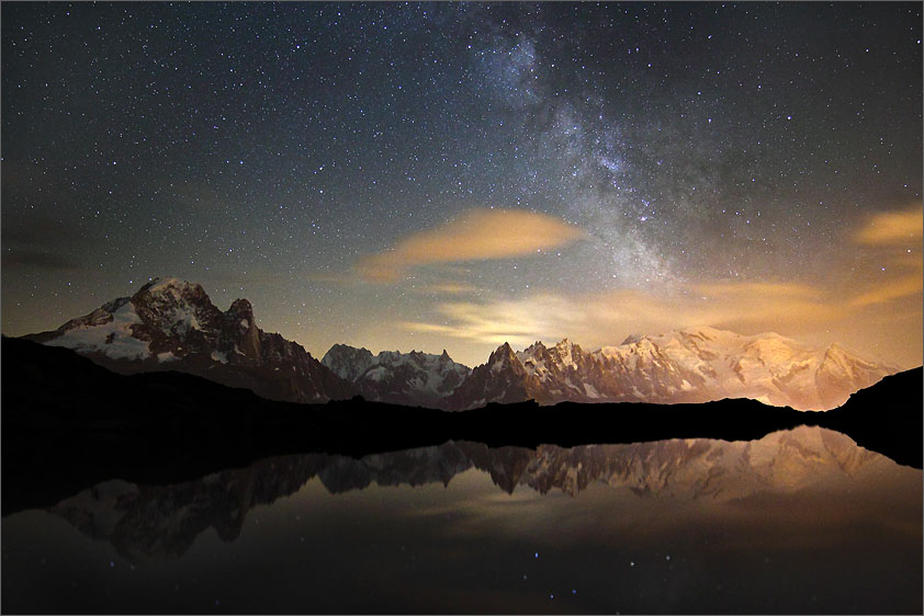 Nighttime Mont Blanc in the French Alps reflecting in alpine lake Lac de Cheserys above Chamonix with the Milky Way