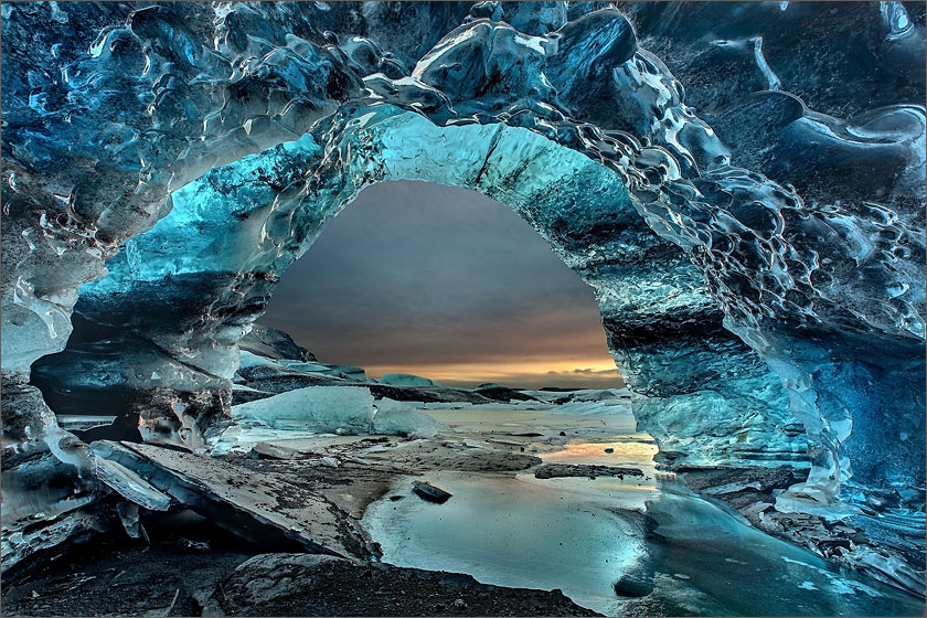 Huge deep blue ice cave within Svínafellsjökull glacier in Skaftafell, Iceland viewed against the sunset