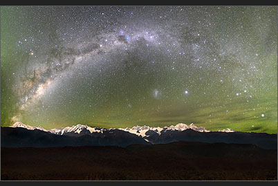 Green Southern Lights envelop the arc of the Milky Way over the New Zealand Alps with Mount Cook and Mount Tasman in an enchanting light