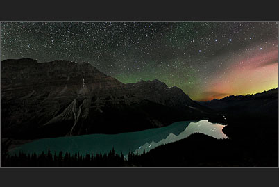 Red and green northern lights with the starry night sky over Peyto Lake in the Canadian Rocky Mountains near Banff
