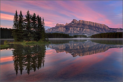 Mount Rundle is reflected in Two Jack Lake near Banff in the Canadian Rocky Mountains at sunrise.